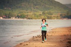 girl runs from distance on beach at low tide - stock photo