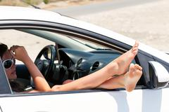 Woman's legs dangling out a car Stock Photos