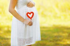 Pregnancy, maternity and new family concept - pregnant woman and heart symbol Stock Photos