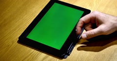A person leafs through a tablet, the background on the device is a chroma key - stock footage