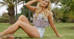 Blond Woman Sitting on Grass and Hugging Knees Stock Footage