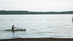 Young man rowing boat passes in front of camera in daytime Stock Footage