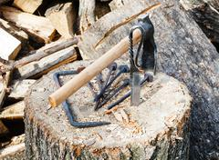 Hew axe and forged hardware on wooden block Stock Photos
