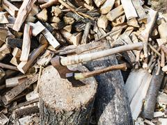 pile of wood, deck for chopping firewood, two axes - stock photo