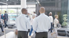 4K Airport security guards on duty, chatting and watching passengers walk by - stock footage