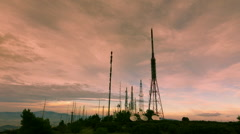 Communication towers antennas site wide view mountain dusk timelapse Stock Footage