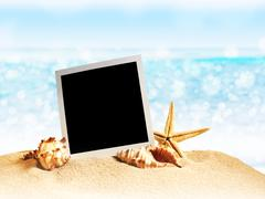 Seashells and old photo frame on sand Stock Photos