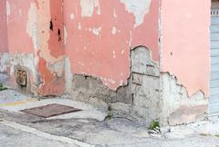 Wall of an old building with ruined plaster. - stock photo