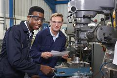Engineer Showing Apprentice How to Use Drill In Factory Stock Photos
