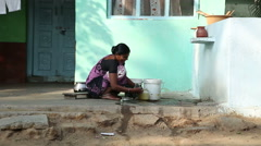 Woman washing pots in front of green painted house in Hampi. Stock Footage