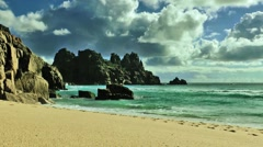 Porthcurno, Cornwall, view onto beach, rocks and clouds Stock Footage