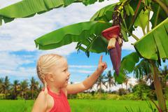 Smiling child exploring the nature - banana flower and fruits - stock photo