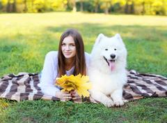 Portrait happy pretty woman and white Samoyed dog resting on the plaid outdoo - stock photo