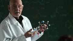 Stock Video Footage of Chemistry teacher holding molecular model, medium shot