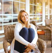 Pretty smiling woman sitting on armchair outdoors in city - stock photo