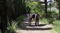 Three pilgrims walking on the paved path to reach the monastery Stock Footage