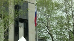 Russian flag limp in the wind in front of Embassy Stock Footage