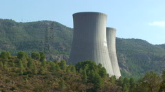 Nuclear cooling towers behind hill with pine forest Stock Footage