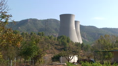 Nuclear cooling towers behind hill with pine forest - stock footage