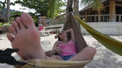 Relaxing in hammock on island beach at Koh Phangan. Foot close up - stock footage