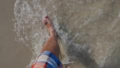 Stock Video Footage of Man walking bare foot on sandy beach into ocean water. Slow motion point of view