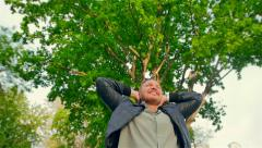 Middle-aged man on a background of spring tree enjoying life Stock Footage