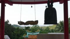 Young girl strikes a iron gong bell in the asian chinese temple. Silhouette Arkistovideo