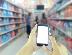 Hand holding smart phone with blur supermarket background Stock Photos