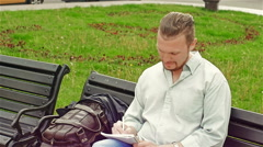 Adult, attractive man sitting on a bench making entries in the notebook - stock footage