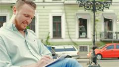 Adult, attractive man sitting on a bench making entries in the notebook Stock Footage
