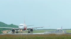 AirAsia Airbus 320 and Thai Airways Airbus 330 taxiing on runway Stock Footage