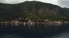 Sail boat sailing the Kotor Bay by beautiful village in Montenegro - stock footage