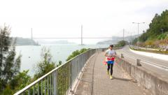 People running and biking on seafront road, sports lifestyle Stock Footage