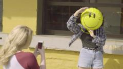 Girl Poses With Smiley Face Balloon, Her Friend Takes Photos Of Her Stock Footage