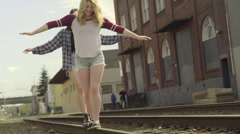 Two Friends Walk Along Train Tracks, Arms Outstretched, Balancing (Slow Motion) Stock Footage