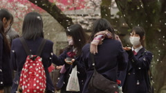 Sakura raining down on Japanese High School Students - stock footage