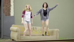 Two Teens Jump Up And Twirl Around On An Old Couch In An Industrial Setting Stock Footage