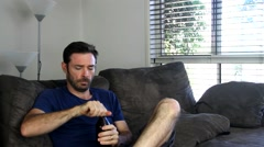 Realistic Australian male drinking beer on chair opening bottle with teeth Stock Footage