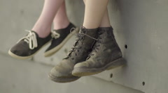 Closeup Of Two Teen's Feet Hanging Over The Edge Of A Wall (Slow Motion) Stock Footage