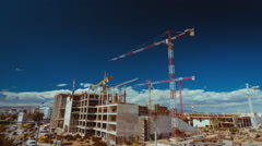 Construction site trucks,machinery,workers,cranes, wide view timelapse Stock Footage