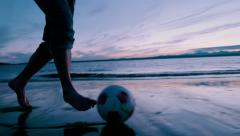 Man Dribbling Soccer Ball up Beach at Sunset - stock footage