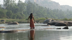 Indian man with long hair walking at the riverbank. Stock Footage