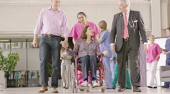 4K Caring medical staff in modern hospital help a patient in a wheelchair Stock Footage