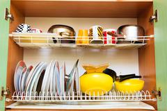 Dirty grubby drainer with clean dishes in kitchen. Stock Photos