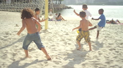 Kids playing soccer on a beach in Brazil Stock Footage
