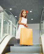 Cute little girl with shopping bags in the mall - stock photo