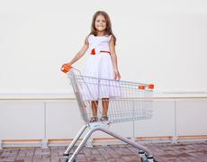 Beautiful little girl in shopping cart having fun outdoors against the white  - stock photo