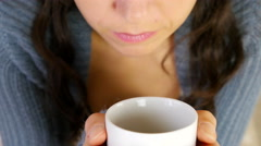 Woman in warm vest sipping her hot drink / coffee / tea Stock Footage