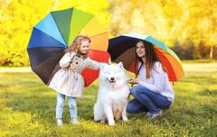 Family, leisure, weather and people concept - mother with child and dog walks Stock Photos