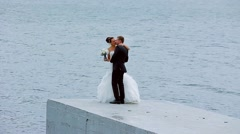Bride and groom cute kissing and cuddling on the background of the sea. - stock footage